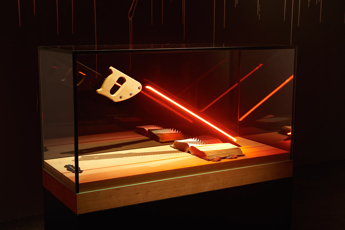 Hand-blown and coloured neon tube, handsaw, Holy Bible from 1898, glass case